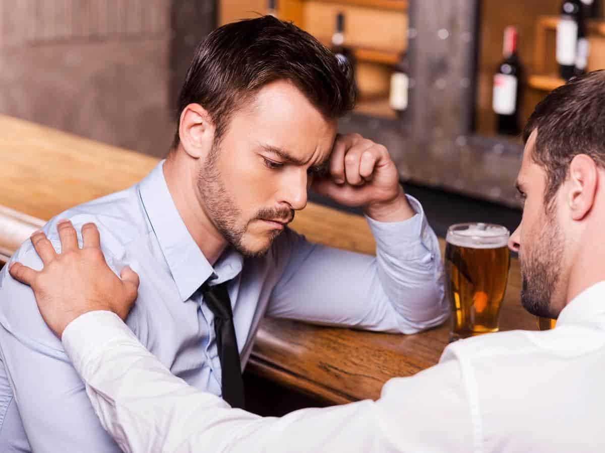 Smutny mężczyzna pocieszany przez przyjaciela Life coaching