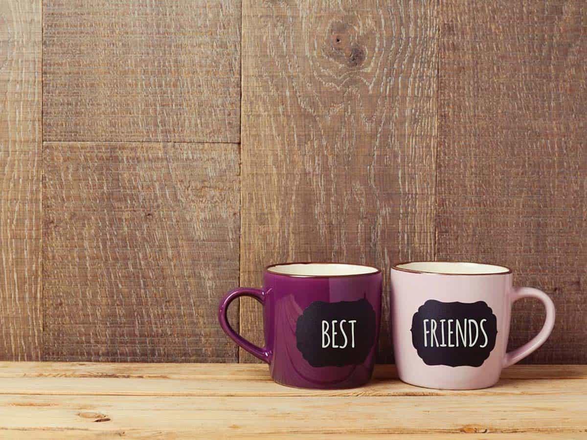 Dwa kubeczki na kawę przyjaciół na tle drewnianej ściany Life coaching