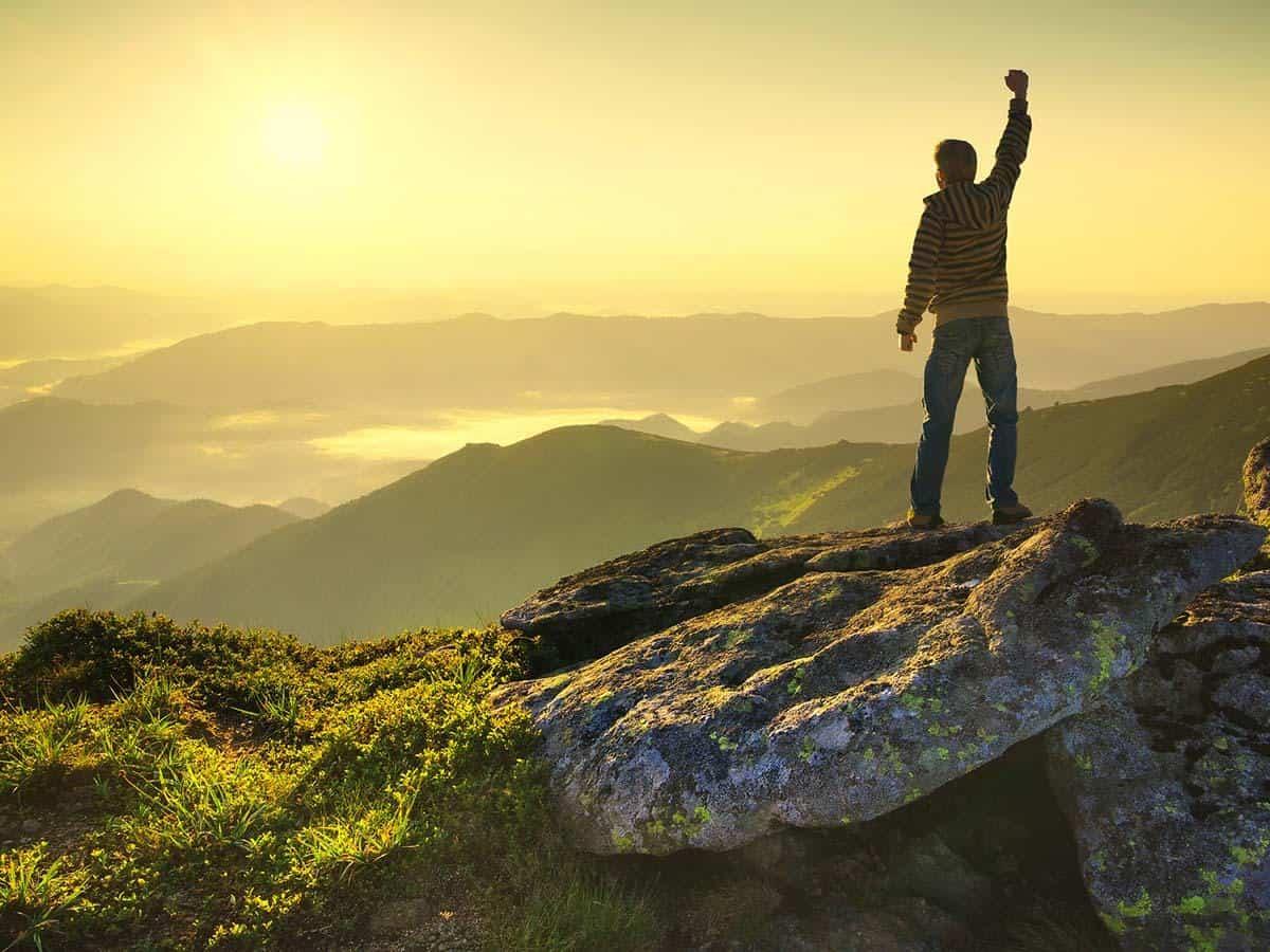 Mężczyzna wznoszący rękę w górę na szczycie góry Life coaching