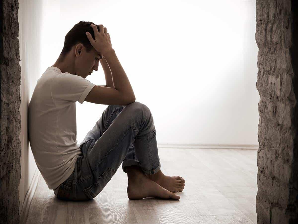 Smutny mężczyzna siedzący na podłodze Life coaching