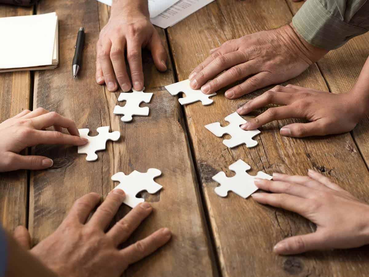 Zespół ludzi układa puzzle