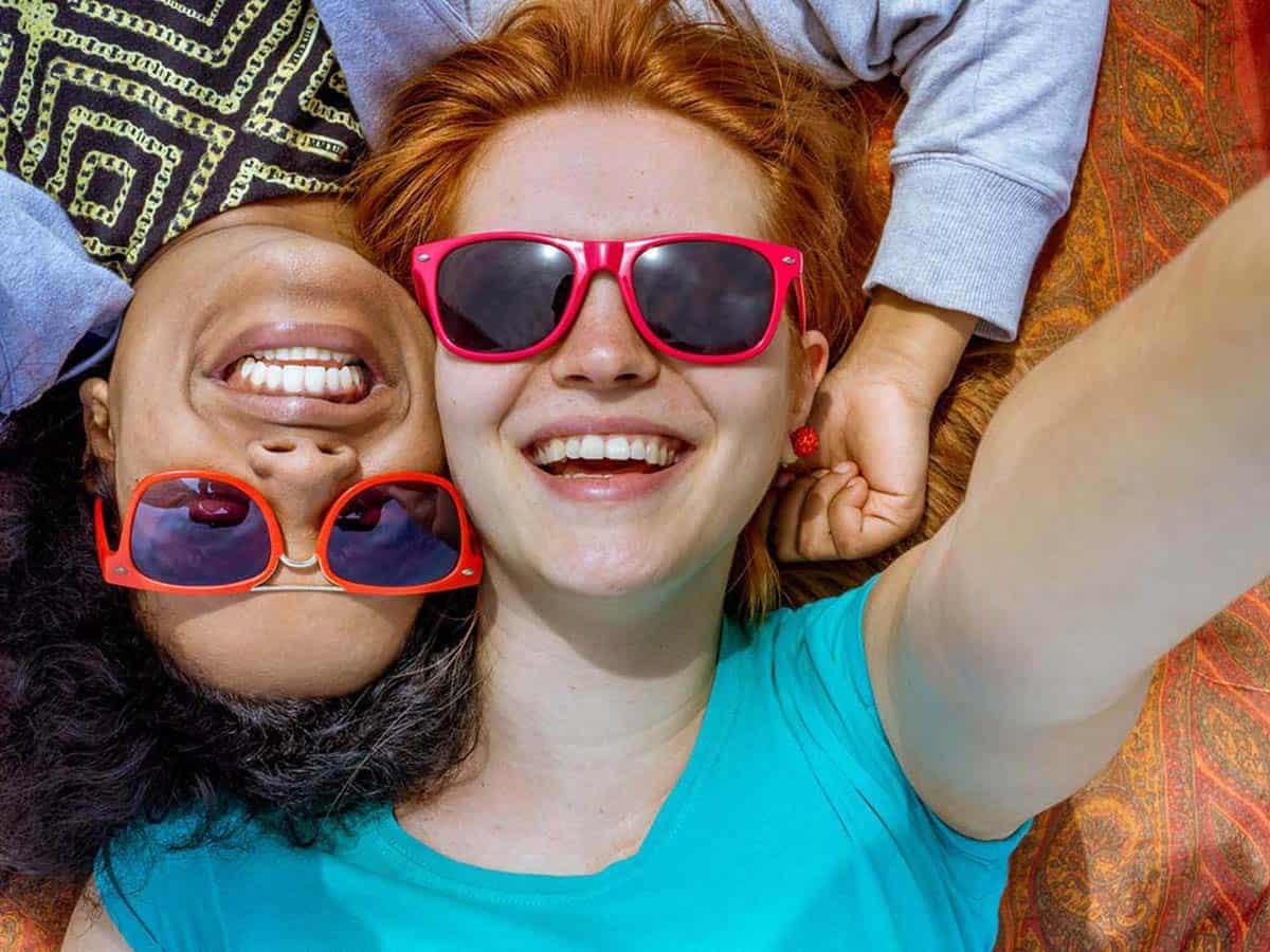 Dwie uśmiechnięte przyjaciółki w okularach przeciwsłonecznych Life coachhing
