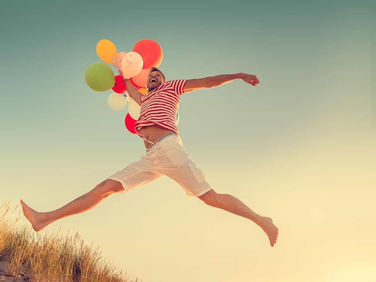 Szczęśliwy mężczyzna z balonikami Szczęście, radość Life Coaching