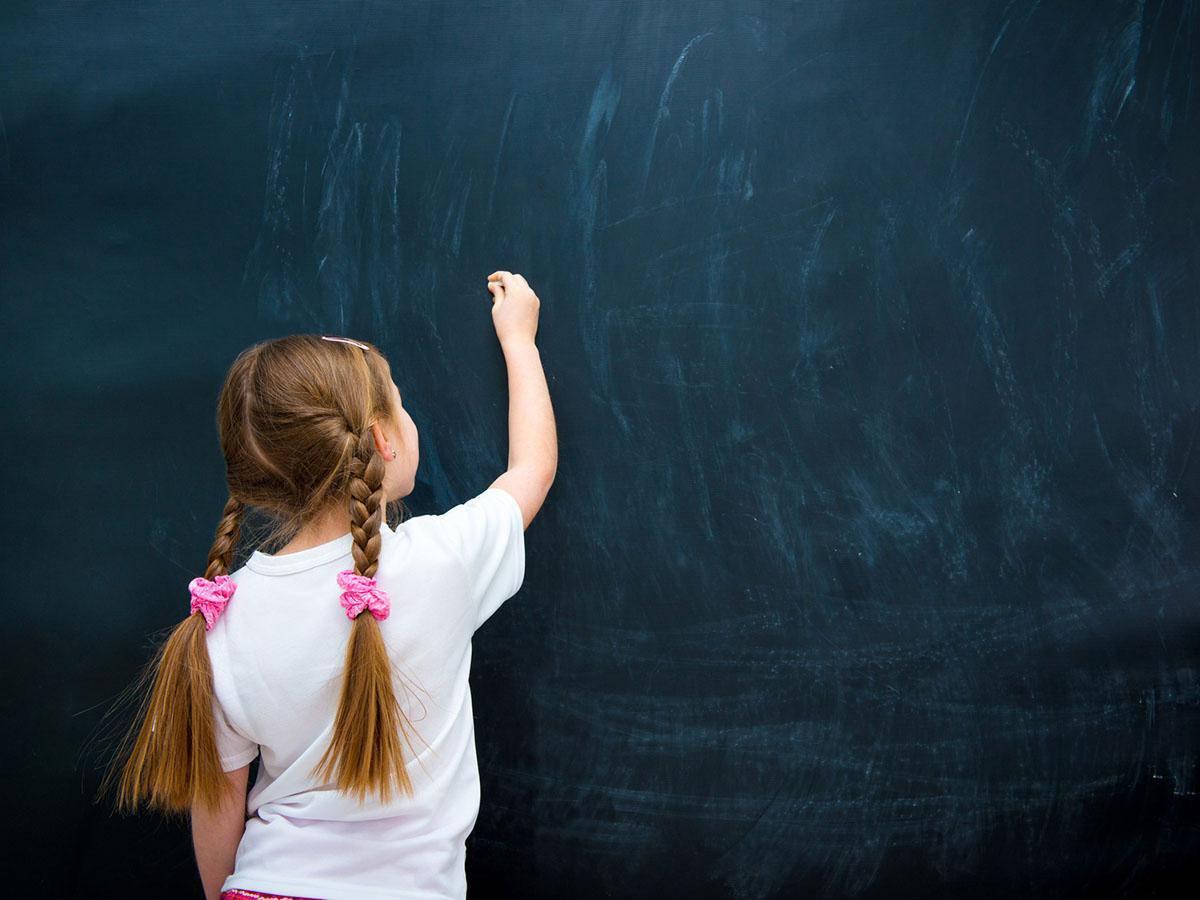 Mała dziewczynka pisze kredą na tablicy Life coaching