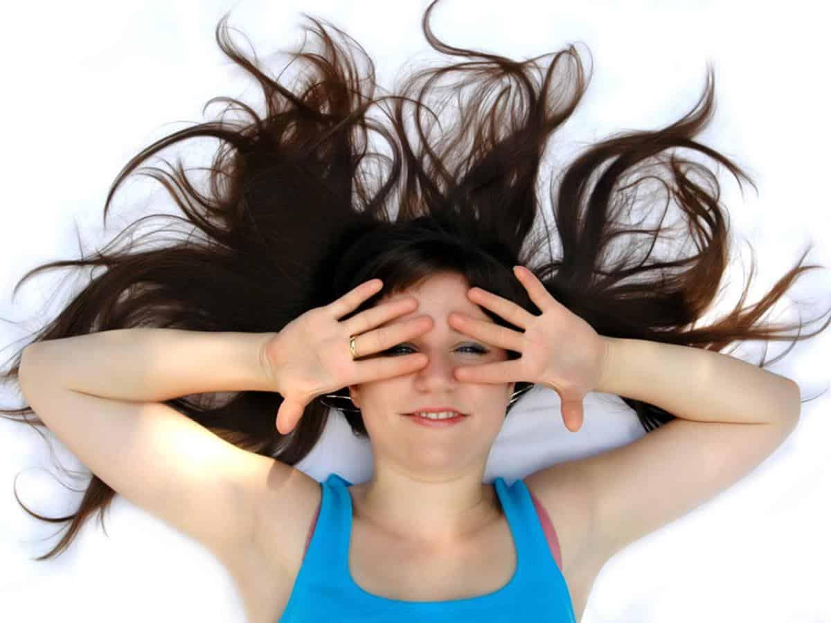 Kobieta z długimi włosami i rękami zasłaniającymi twarz