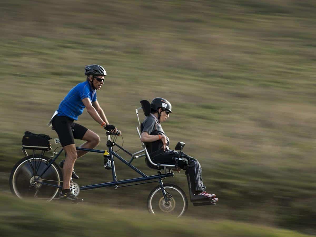 Mężczyzna jedzie z niepełnosprawnym synem na rowerze Life coaching